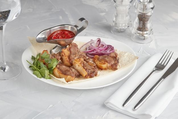 Mięso Z Grilla Na Talerzu, Serwowane W Restauracji, Jasnym Tle Premium Zdjęcia