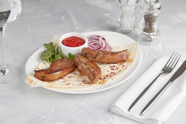 Mięso z grilla na talerzu, serwowane w restauracji, jasnym tle