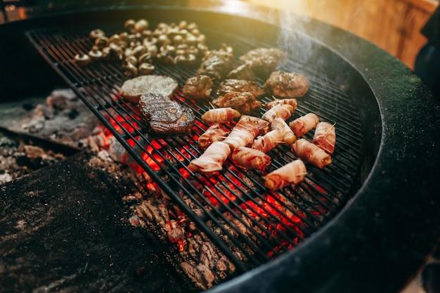 Mięso z grilla w grillu z płomieniami i węglami