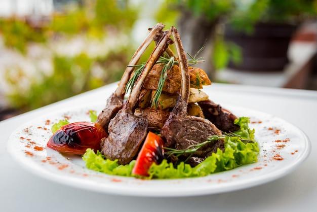 Mięso z kością z warzywami na białym talerzu. restauracja.