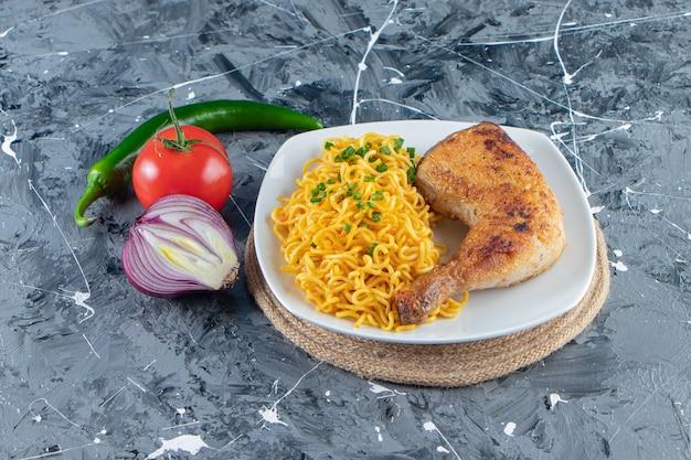 Mięso z kurczaka i makaron na talerzu na trójnogu obok warzyw, na tle marmuru.
