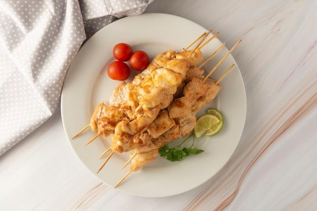 Mięso z kurczaka na szaszłyki bambusowe kebab w białej płytce, marmurowe jasne tło. dieta o niskiej zawartości tłuszczu.