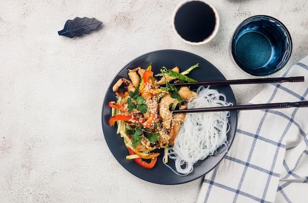 Mięso z kurczaka z warzywnym wokiem i chińskim makaronem ryżowym, sosami i sezamem w czarnej misce z chińskimi pałeczkami na jasnoszarym tle. tradycyjne azjatyckie jedzenie.