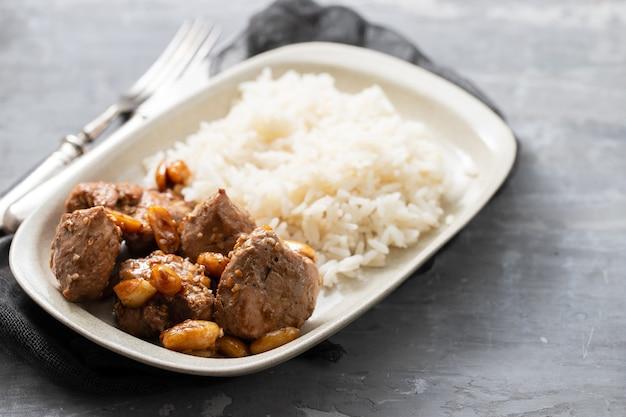 Mięso z orzechami i gotowanym ryżem na białym talerzu na ceramicznym tle