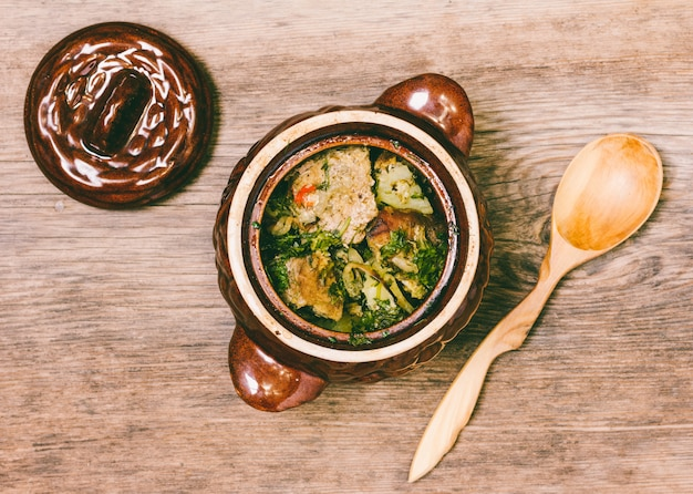 Mięso z ziemniakami w glinianym garnku i drewnianą łyżką na stołowym odgórnym widoku
