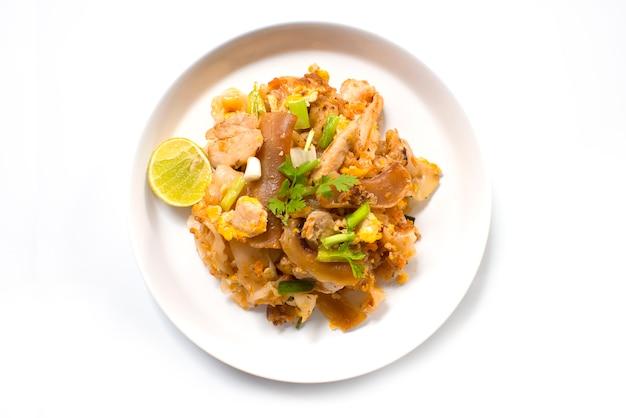 Miesza smażącego płaskiego ryżowego kluski z soj kumberlandem i wieprzowiną w białym naczyniu na białym tle