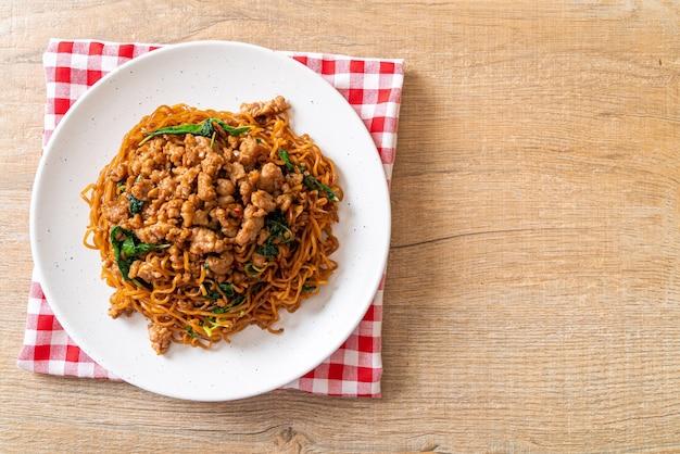 Mieszać, smażony makaron instant z tajską bazylią i mieloną wieprzowiną, azjatyckie jedzenie