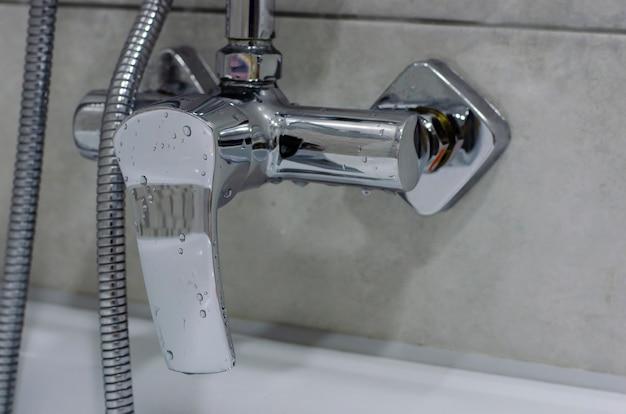 Mieszać zimną gorącą wodę z kroplami wody. nowoczesna łazienka z kranem. kran kuchenny. chromowany metal.