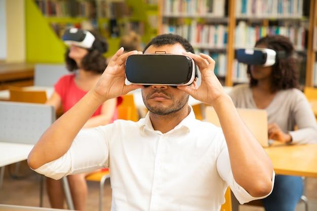 Mieszaj ściganą grupę studentów oglądających wirtualny samouczek wideo