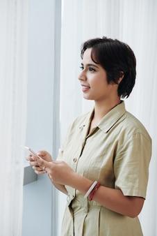 Mieszana biegowa dama w biznes sukni pozyci przy biurowym okno z smartphone i przyglądającym out