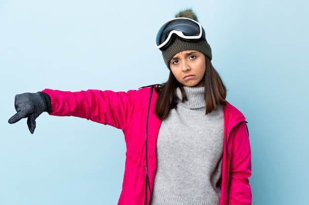 Mieszana biegowa narciarki dziewczyna z snowboardowymi szkłami nad odosobnioną błękit ścianą pokazuje kciuka puszek z negatywnym wyrażeniem