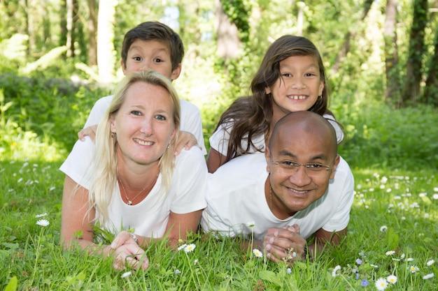Mieszana czteroosobowa rodzina z dwójką dzieci chłopca i dziewczynkę leżącą w trawie latem