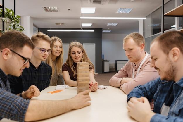 Mieszana drużyna bawić się blokuje drewnianą grę w biurze