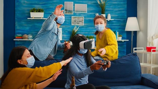 Mieszana grupa ludzi prowadząca czarną kobietę z zestawem słuchawkowym vr grającym w wirtualne gry wideo w salonie, zachowując dystans społeczny agaist covid19. różnorodni przyjaciele bawią się na nowej normalnej imprezie.