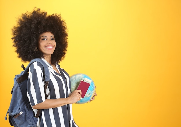Mieszana kobieta afro, z paszportem i kulą ziemską, jedzie na wycieczkę, koncepcja podróży