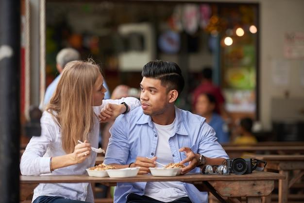 Mieszana para przy plenerową kawiarnią