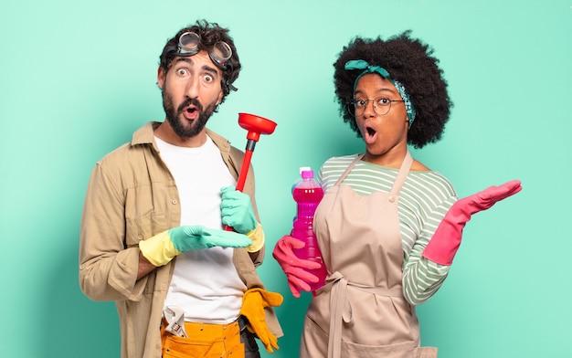 Mieszana para wyglądająca na zaskoczoną i zszokowaną, z opuszczoną szczęką, trzymając przedmiot z otwartą ręką z boku. koncepcja sprzątania .. koncepcja naprawy domu
