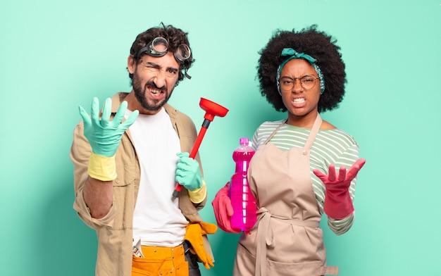 Mieszana para z szeroko otwartymi ustami i oczami oraz dłońmi na brodzie czująca się nieprzyjemnie zszokowana mówiąca co lub wow koncepcja sprzątania koncepcja naprawy domu