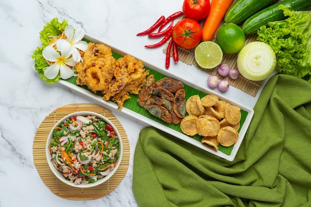 Mieszana pikantna sałatka z wietnamską kiełbasą, konserwowanym jajkiem i chrupiącymi kalmarami, tajskie jedzenie.