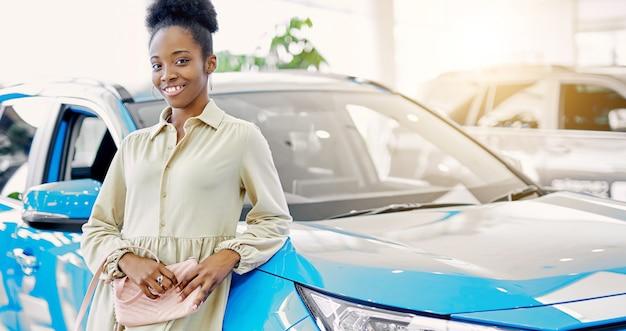 Mieszana rasa african american kobieta pozuje obok niebieskiego samochodu w salonie