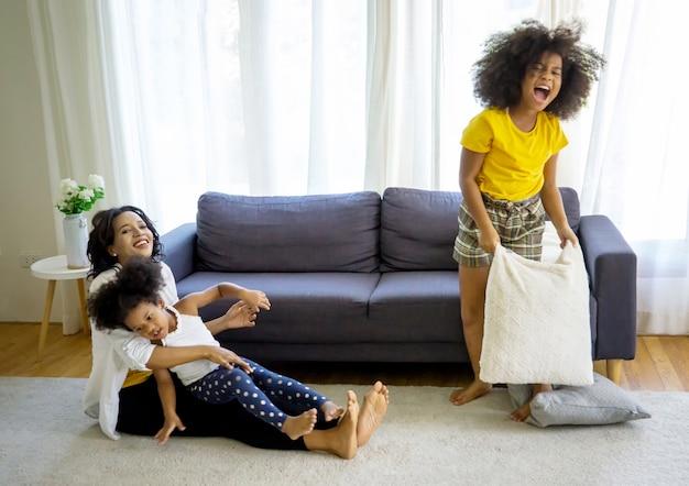 Mieszana rasa rodziny, taty, mamy i córek bawi się razem w salonie