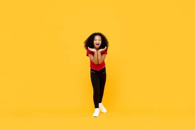 Mieszana rasy dziewczyna afro w zaskoczony podekscytowany gest rękami otworzyć na białym tle na żółtej ścianie