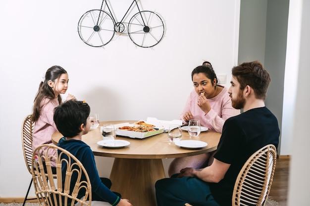 Mieszana rodzina jedząca przy stole wegańską pizzę w domu. wegańska żywność naturalna. różnorodność i prawdziwi ludzie