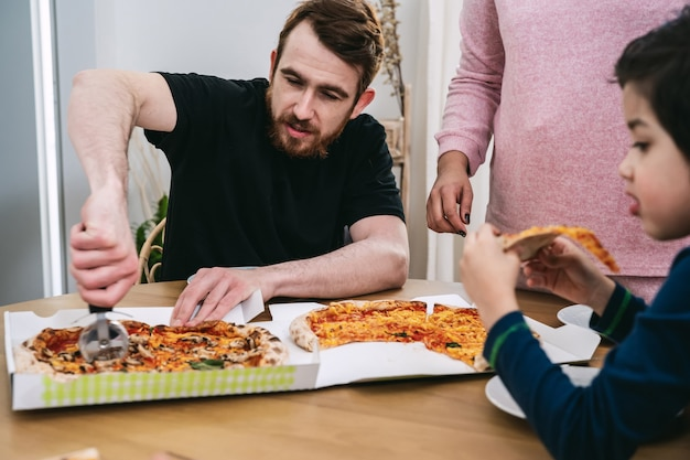 Mieszana rodzina jedząca w domu wegańską pizzę z naturalnych składników. wegańskie jedzenie. różnorodność i prawdziwi ludzie