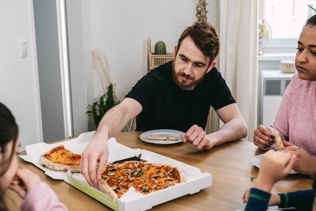 Mieszana rodzina jedząca w domu wegańską pizzę z pomidorami, pieczarkami i wegańskim serem. wegańskie jedzenie. różnorodność i prawdziwi ludzie