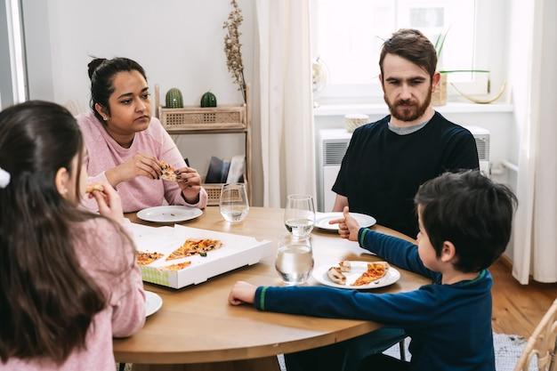 Mieszana rodzina siedząca przy stole i jedząca w domu wegańską pizzę z naturalnych składników. wegańskie jedzenie. różnorodność i prawdziwi ludzie