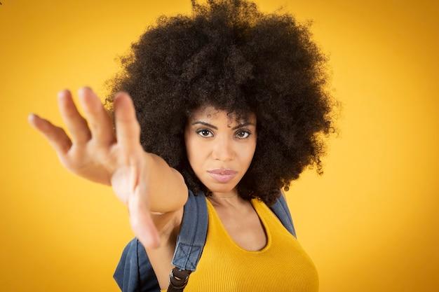 Mieszane afro american kobieta z plecakiem i wyciągniętą ręką, koncepcja podróży, żółte tło
