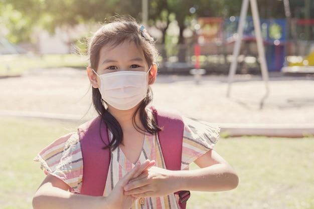 Mieszane azjatyckie dziewczyny noszące maskę i stosujące środek dezynfekujący do rąk, ponowne otwarcie szkoły