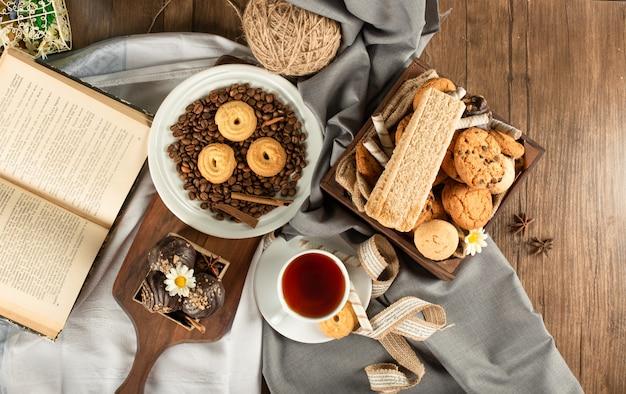 Mieszane ciasteczka, filiżanka herbaty i książka