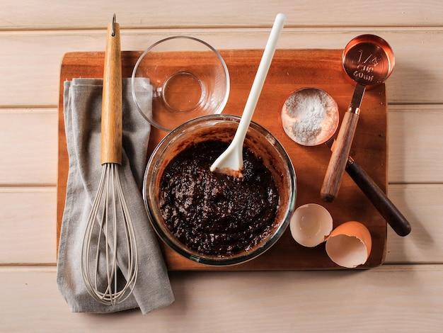 Mieszane ciasto czekoladowe na przezroczystej misce z białą łopatką, pieczenie krok po kroku w kuchni, robienie ciasta czekoladowego lub brownies