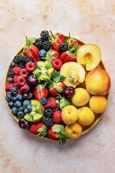 Mieszane jagody flat lay z brzoskwiniami i fotografia żywności kiwi