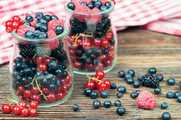 Mieszane jagody w szklanym słoju na brązowym drewnianym stole