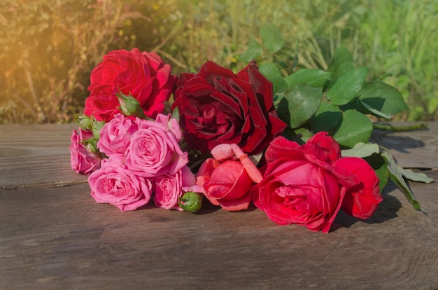 Mieszane kolorowe róże pełne kwitnienia. piękno kwiatów róż. wspaniałe kwiaty na drewnianym tle.