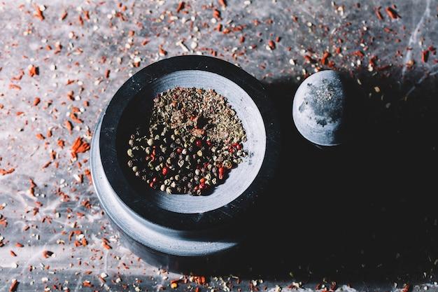 Mieszane kolorowe ziarna pieprzu w moździerzu
