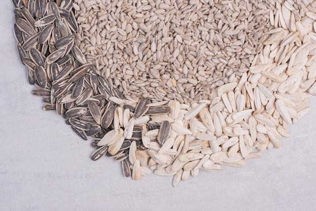 Mieszane nasiona słonecznika na białej powierzchni.