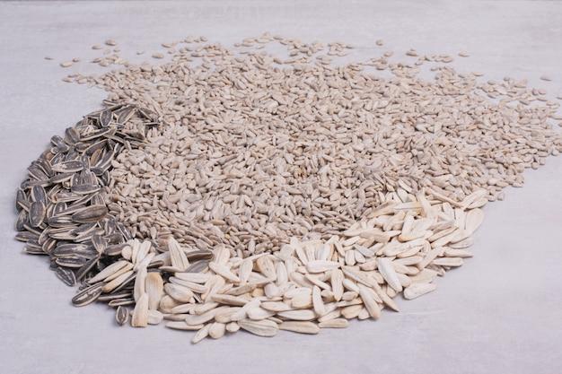 Mieszane nasiona słonecznika rozrzucone na białej powierzchni.
