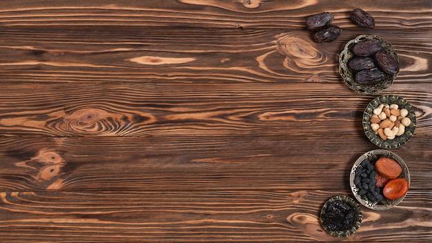 Mieszane orzechy; daty i suszone owoce na festiwalu ramadan na tle drewnianych