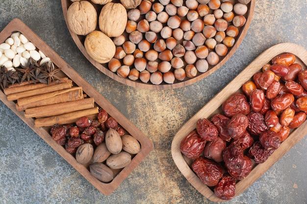 Mieszane orzechy z laskami cynamonu i suszonymi owocami na drewnianym talerzu. wysokiej jakości zdjęcie