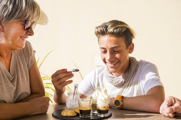 Mieszane pokolenia ludzi rasy kaukaskiej razem jedzących śniadanie w poranek na świeżym powietrzu. stary i młody mężczyzna i kobieta rodzina babcia i siostrzeniec