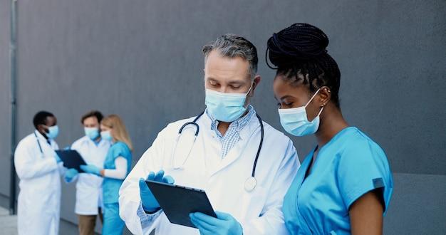 Mieszane rasy para mężczyzny i kobiety, koledzy lekarzy w maskach medycznych pracujących i używających tabletu. wielu etnicznych lekarzy płci męskiej i żeńskiej dotykając i przewijając komputer gadżet.