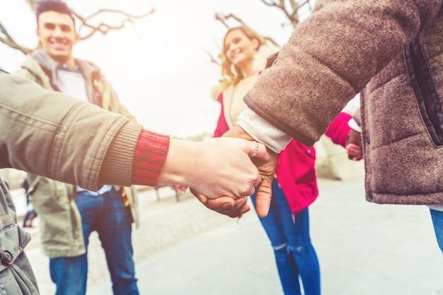 Mieszane rasy przyjaciół trzymając się za ręce w kręgu