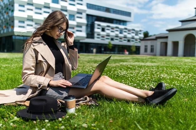 Mieszane rasy studentka siedzi na trawie pracy na laptopie w kampusie