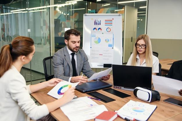 Mieszane rasy współpracownicy analizujący różne dokumenty biznesowe i pracujący z komputerami przy stołach w nowoczesnym biurze.