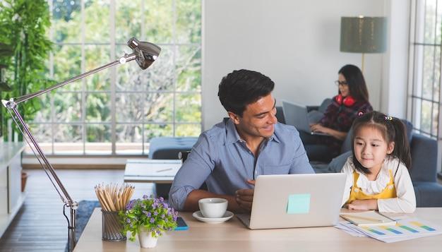 Mieszane rodziny rasy przebywających razem, kaukaski ojciec siedzi i pracuje przy biurku i uczy pół-rasy córeczka cute białych azjatyckich matka przy użyciu komputera przenośnego na kanapie. pomysł na pracę w domu.