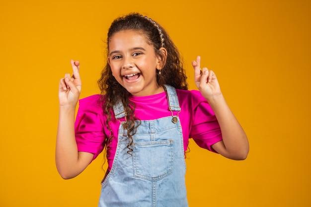 Mieszane śmieszne dziewczynka skrzyżowanie palców, mając nadzieję, że jej życzenie się spełni, na białym tle na żółtym tle. portret małej dziewczynki modlącej się, życzącej powodzenia lub cudu