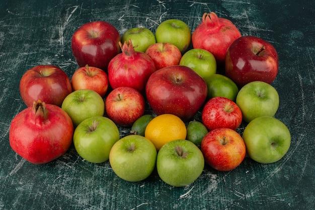 Mieszane świeże owoce rozrzucone na marmurowej powierzchni.